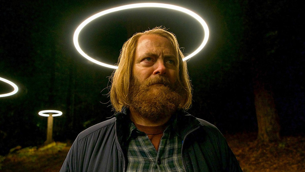 A blonde man with long hair and a bear stands in forest under halo shaped LED lights