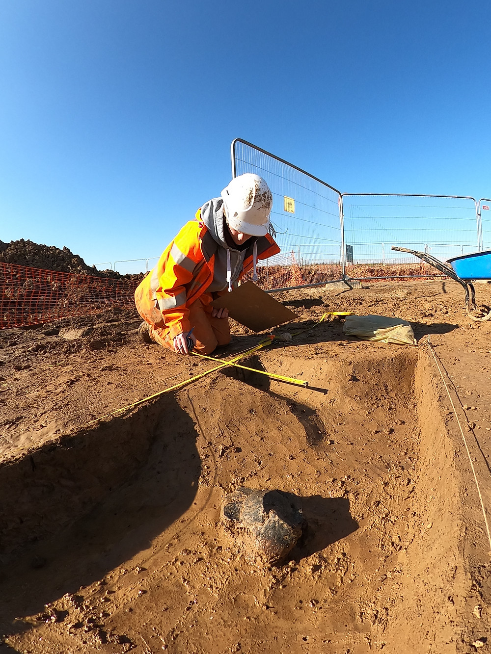 A lady holding a tape measure and wearing orange PPE and a white hard hat kneels on the muddy ground. In front of her is a black pot in the bottom of an excavated ditch.