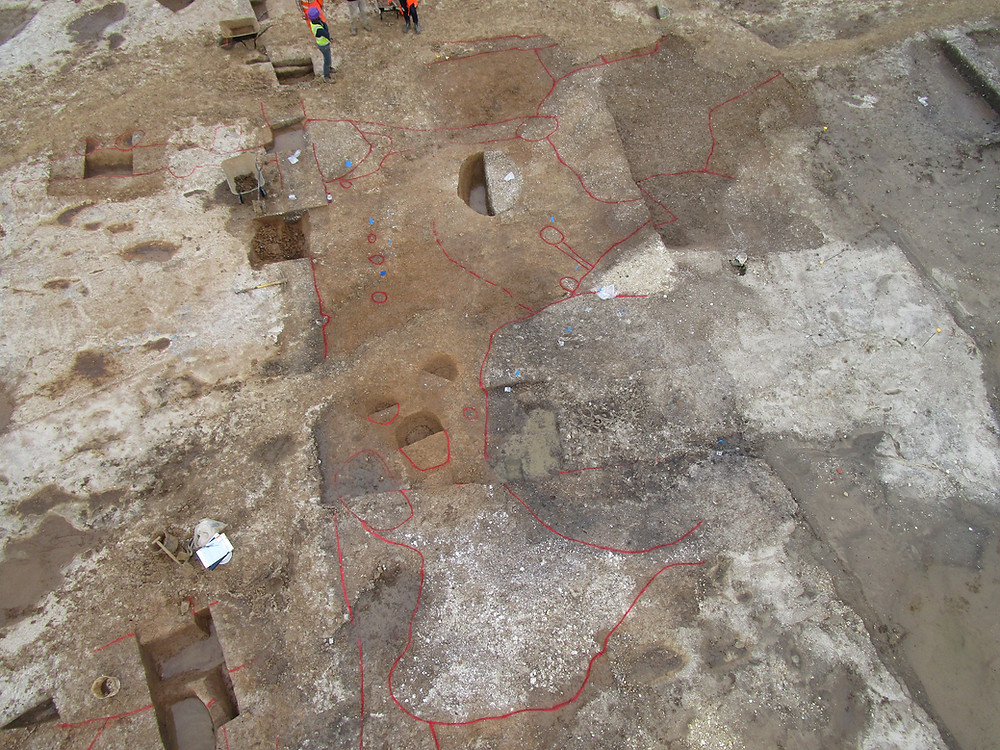 An aerial shot of different coloured soils representing archaeological features. Spray paint has been used to highlight the location of the features.