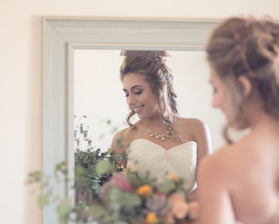 Messy fish tail braid with cascading petals through strands of the hair, cute little rose buds & hair vine ornamenting the hair. Natural, clean & seamless makeup with a pop of pistachio color on the eyes adds to the entire look & charm of bohemian wedding vibe!