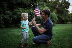 Timothy Barr and daughter Dixie holding American flag.