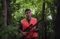 Timothy Barr standing in woods in hunting gear.