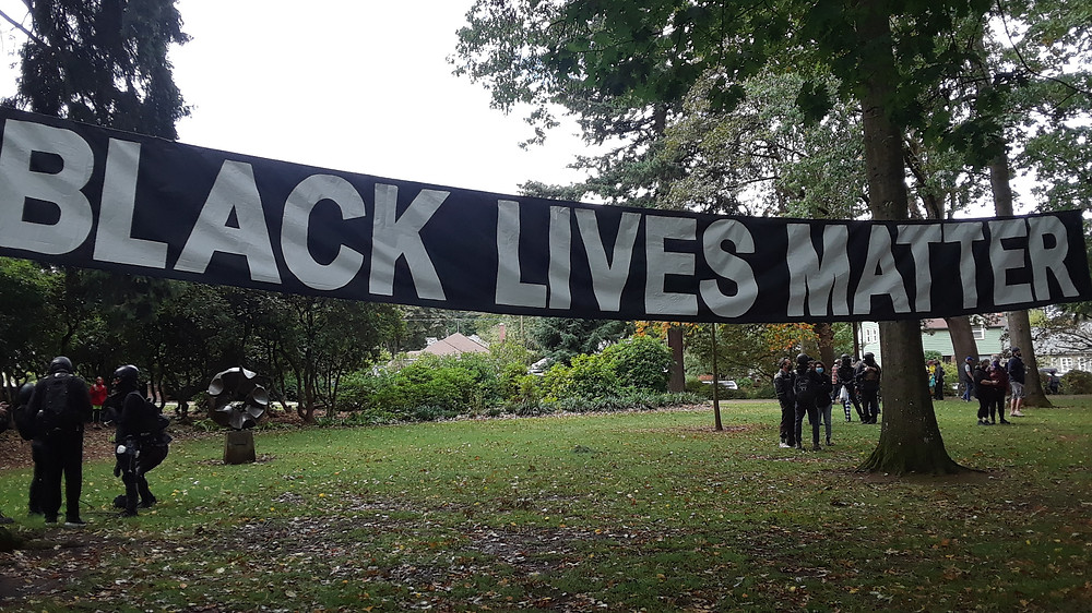 "A large banner at Peninsula Park reading ""BLACK LIVES MATTER"""