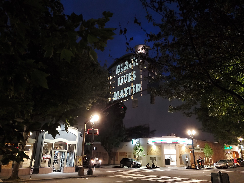 """Massive words """"Black Lives Matter"""" projected onto the side of the Hatfield Courthouse at night."""