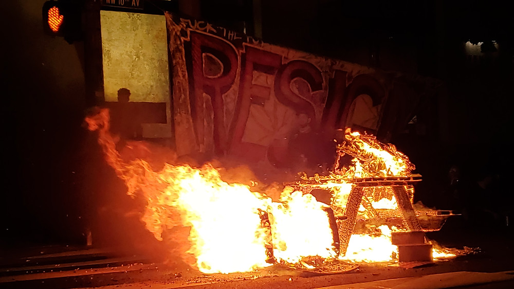A flaming picnic table with a large banned reading RESIGN in the middle of the street in the Pearl at night.