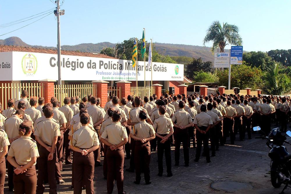 Alunos do colégio da polícia militar estão saudando as bandeiras.