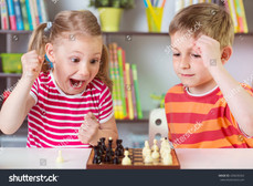 stock-photo-two-cute-children-playing-chess-at-home-439639354.jpg