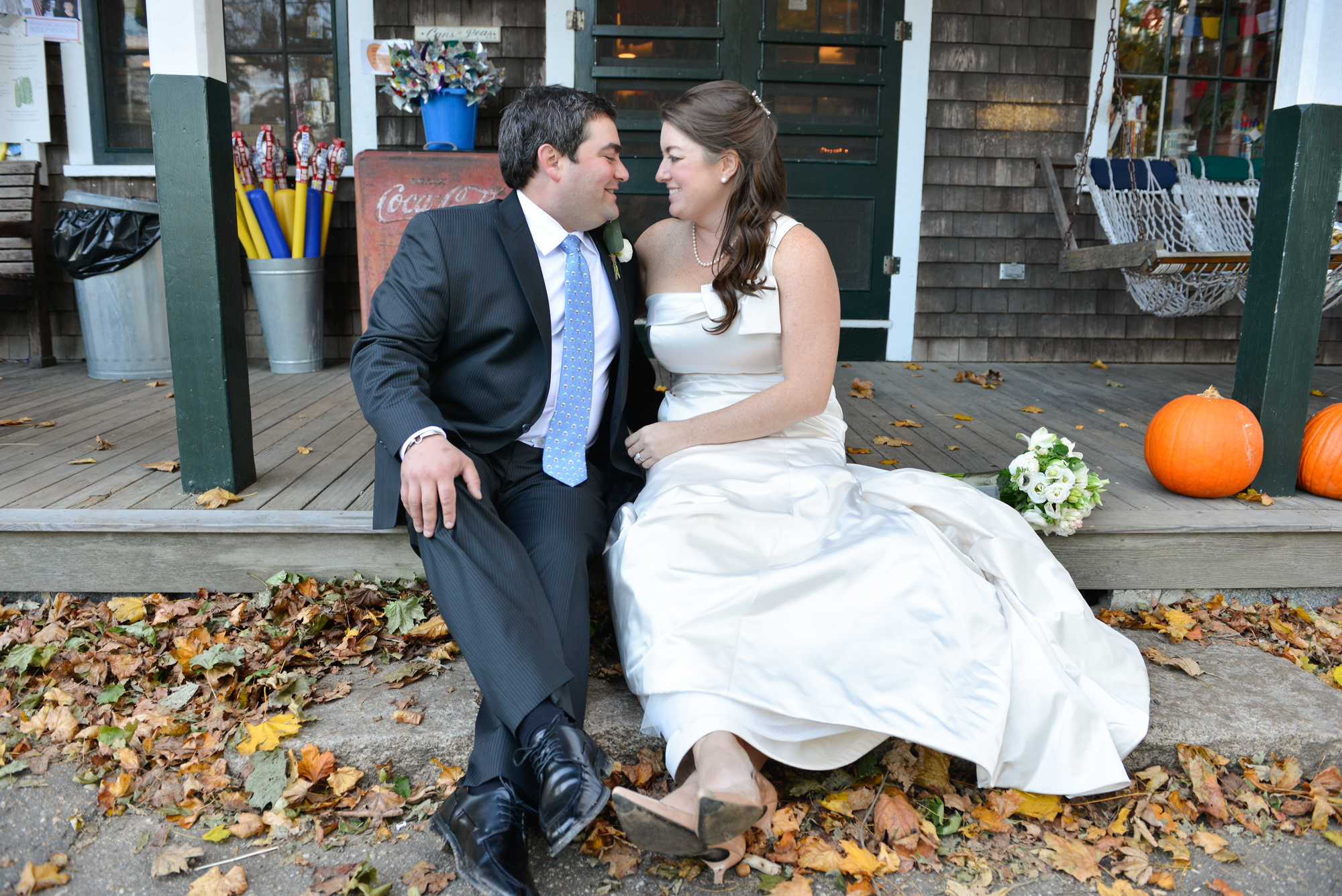 A bride and groom sitting on the steps of Alley's General Store in West Tisbury photo by David Welch Photography