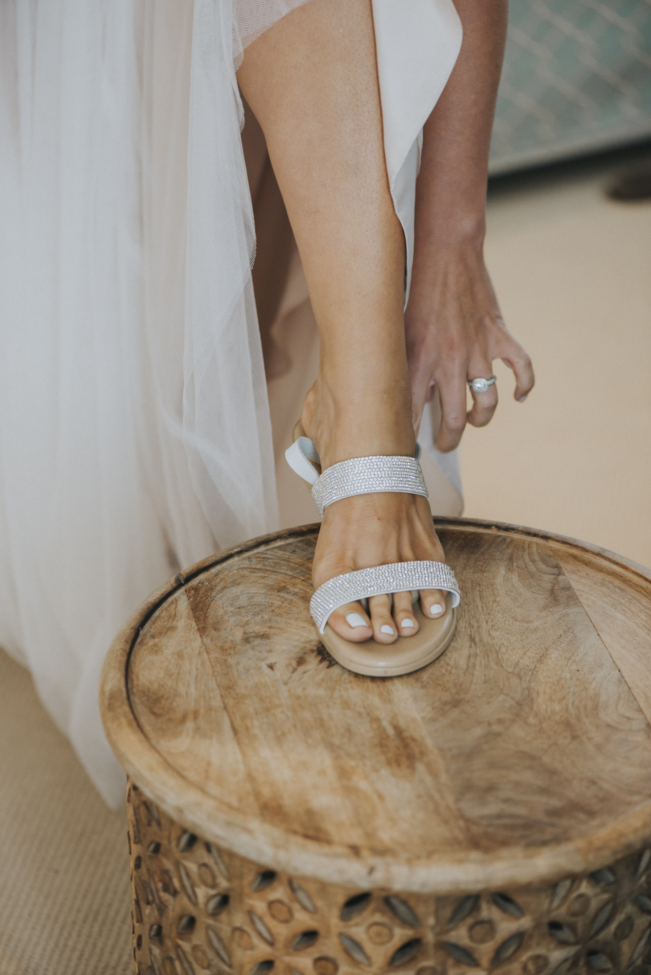 A bride putting on her wedding shoes at the Harbor View Hotel photo by David Welch Photography