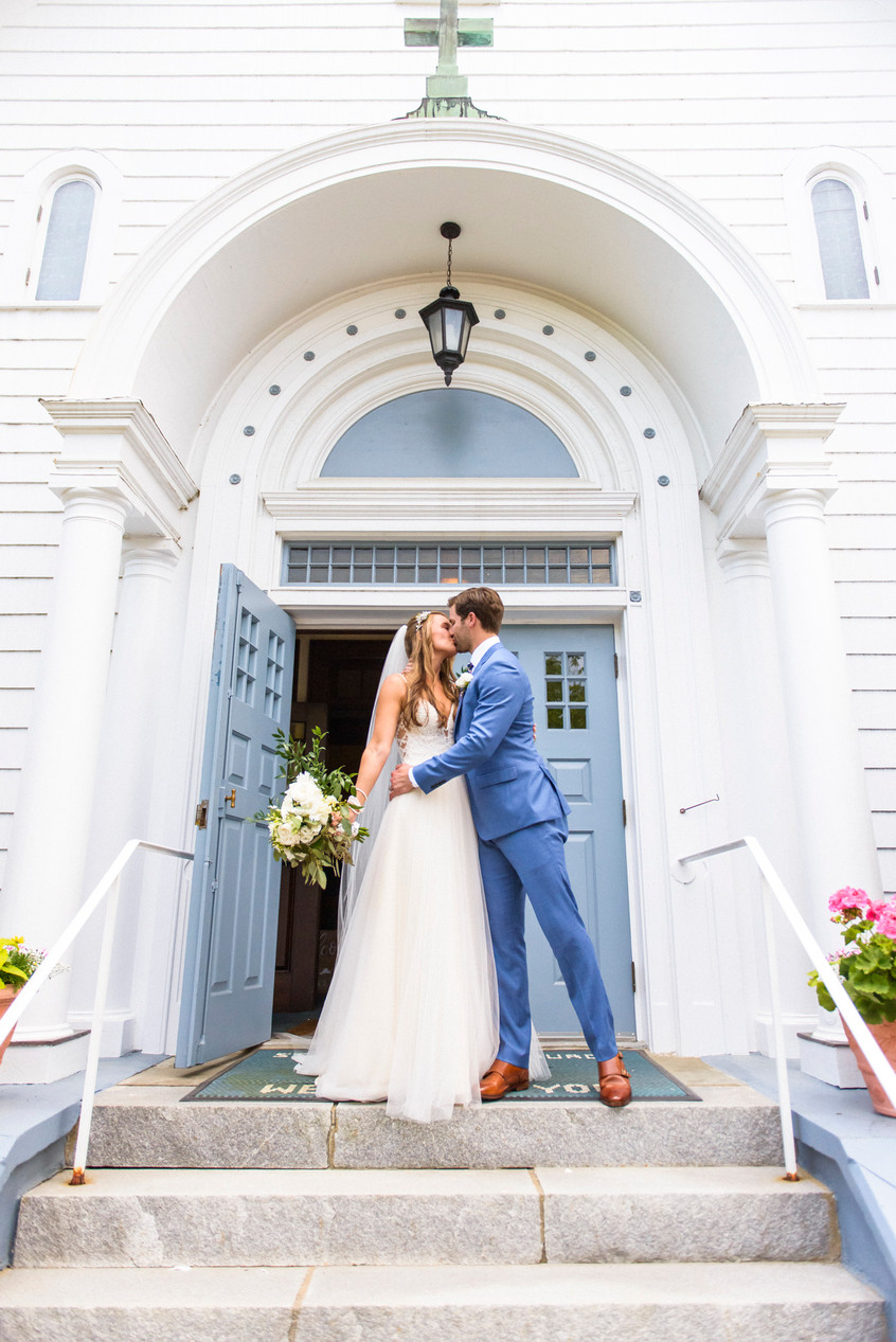 A bride and groom kiss outside St. Elizabeth's Church in Edgartown photo by David Welch Photography