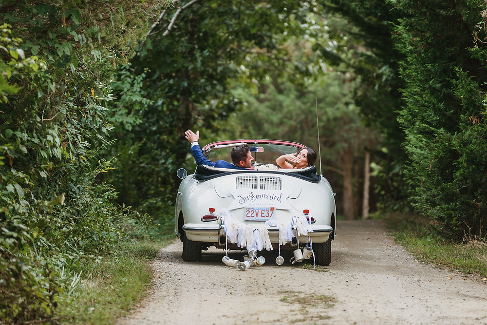 A bride and groom driving away in a Porsche in Edgartown photo by David Welch Photography
