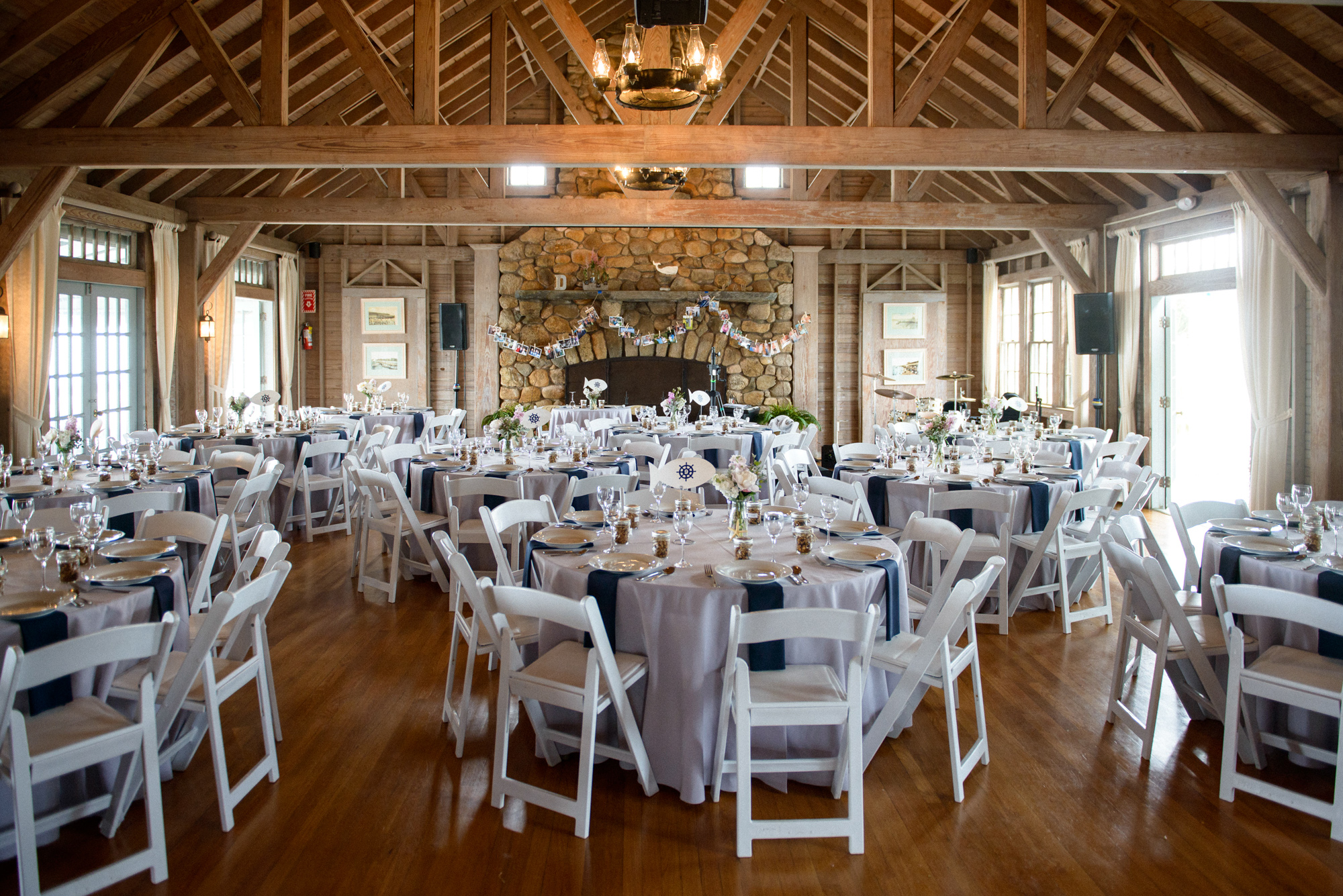 A wedding reception room with decorated tables at the East Chop Beach Club in Oak Bluffs  photo by David Welch Photography