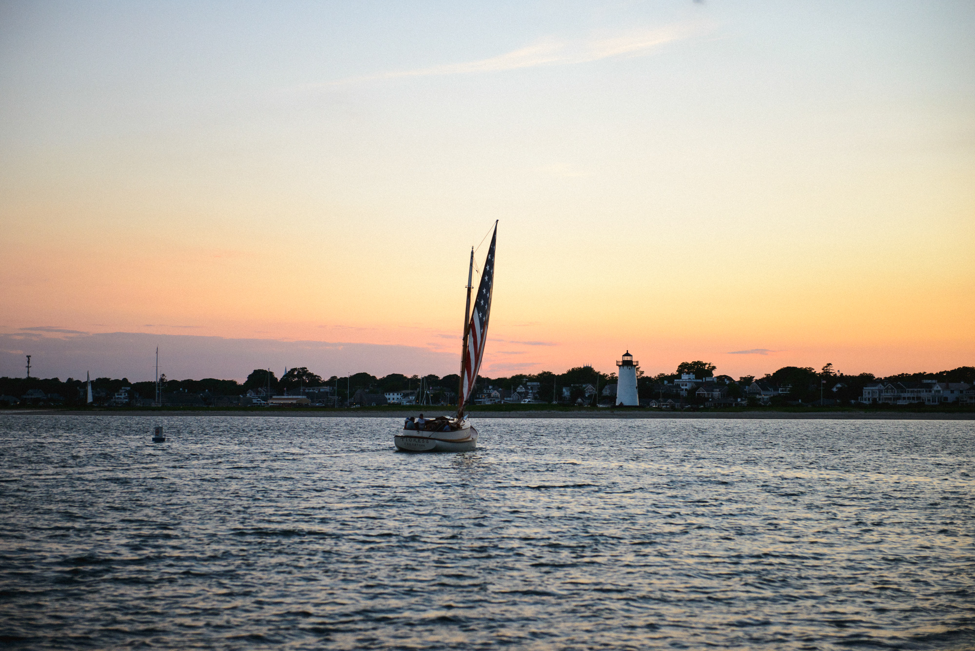 The catboat Tigress sails into the sunset near the Edgartown Lighthouse photo by David Welch Photography