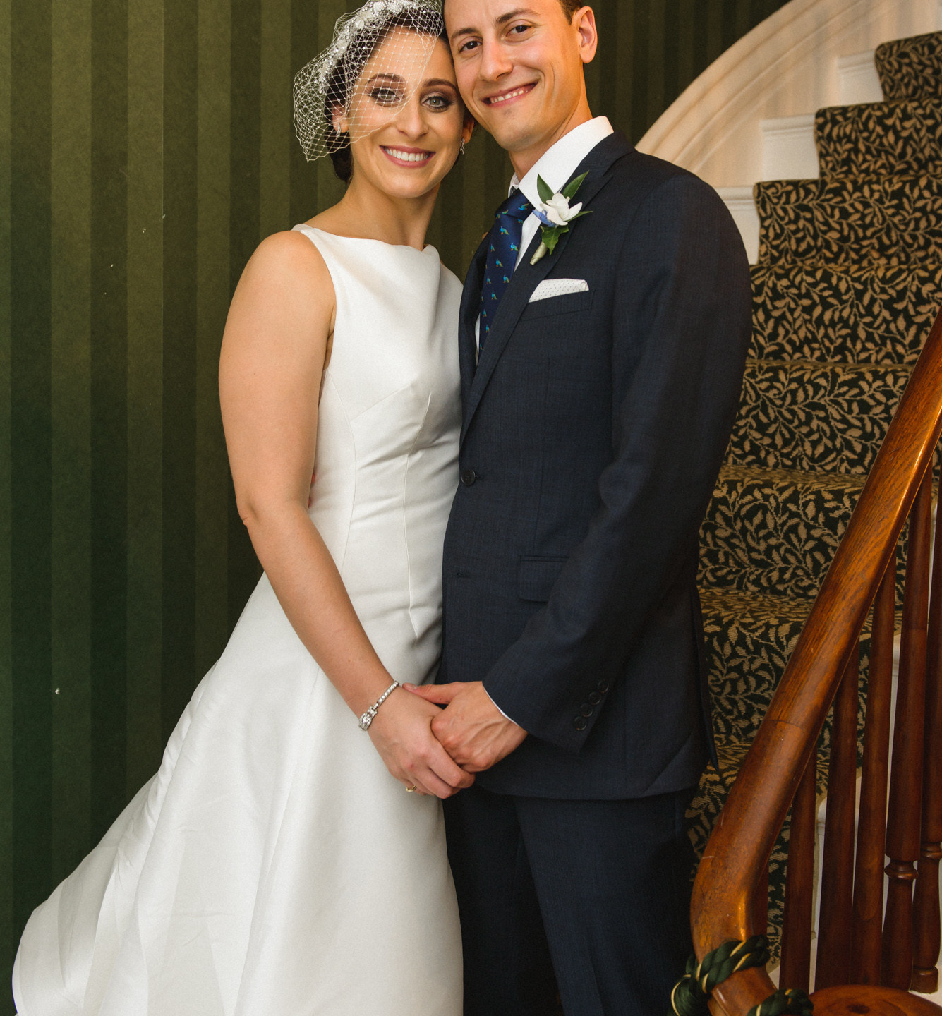 A bride and groom standing on the ornate staircase inside the Dr. Daniel Fisher House Edgartown  photo by David Welch Photography