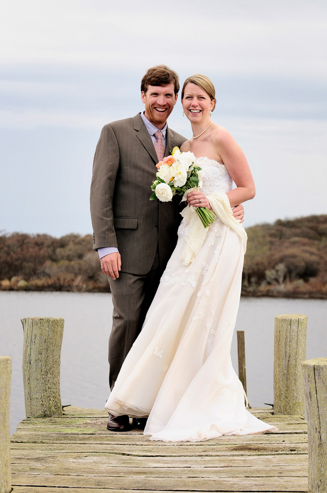 A bride and groom stand on a small pier near the Allen Sheep Farm in Chilmark photo by David Welch Photography