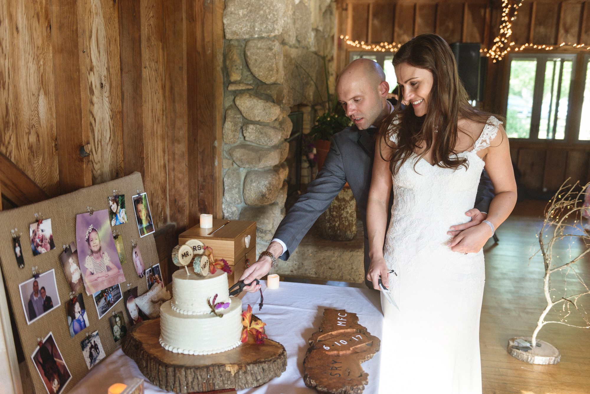 A bride and groom cutting a wedding cake near the fireplace inside the mainstay at the Sailing Camp Park in Oak Bluffs photo by David Welch Photography