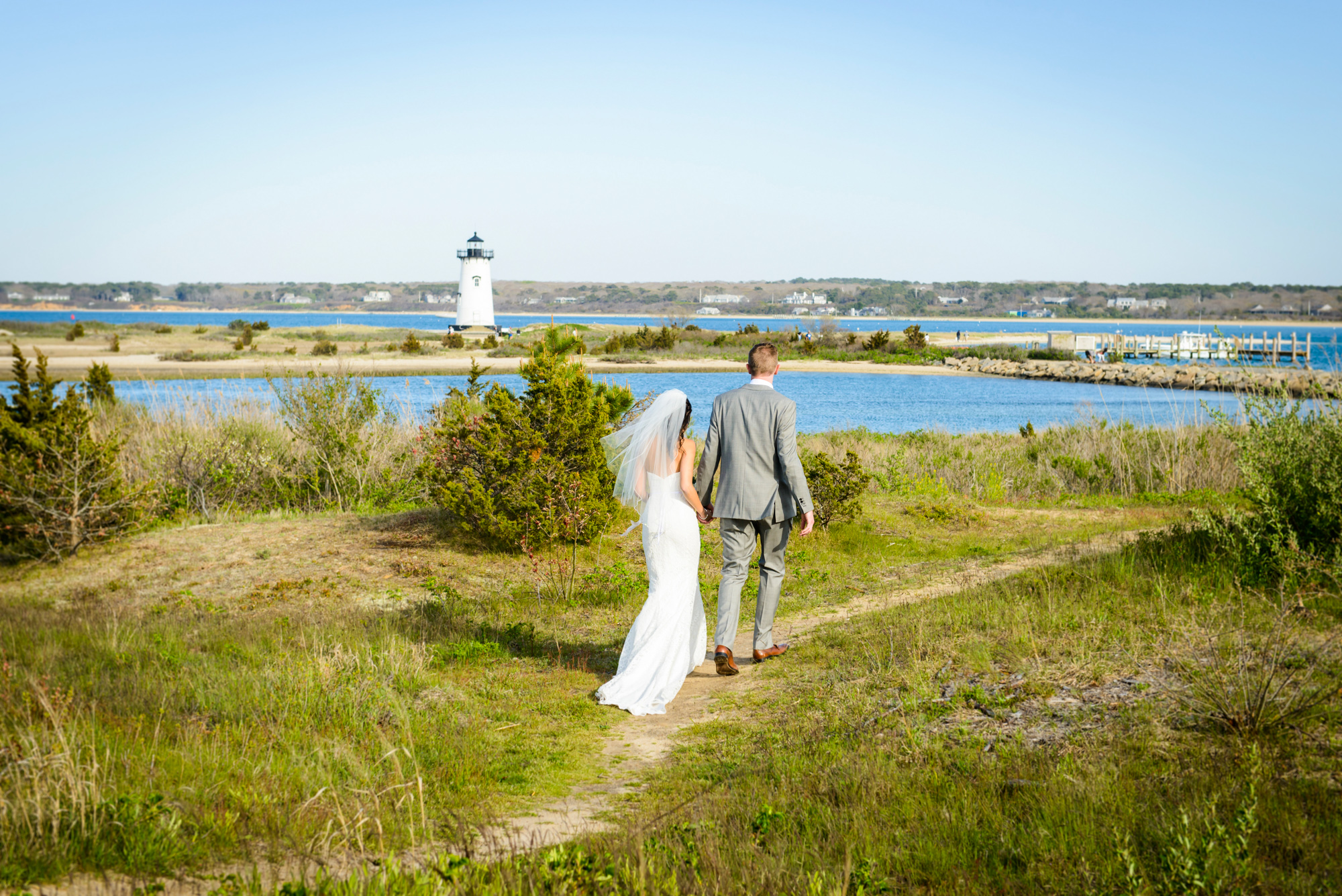 Walking towards the Edgartown Lighthouse during a Harbor View Hotel wedding  photo by David Welch Photography