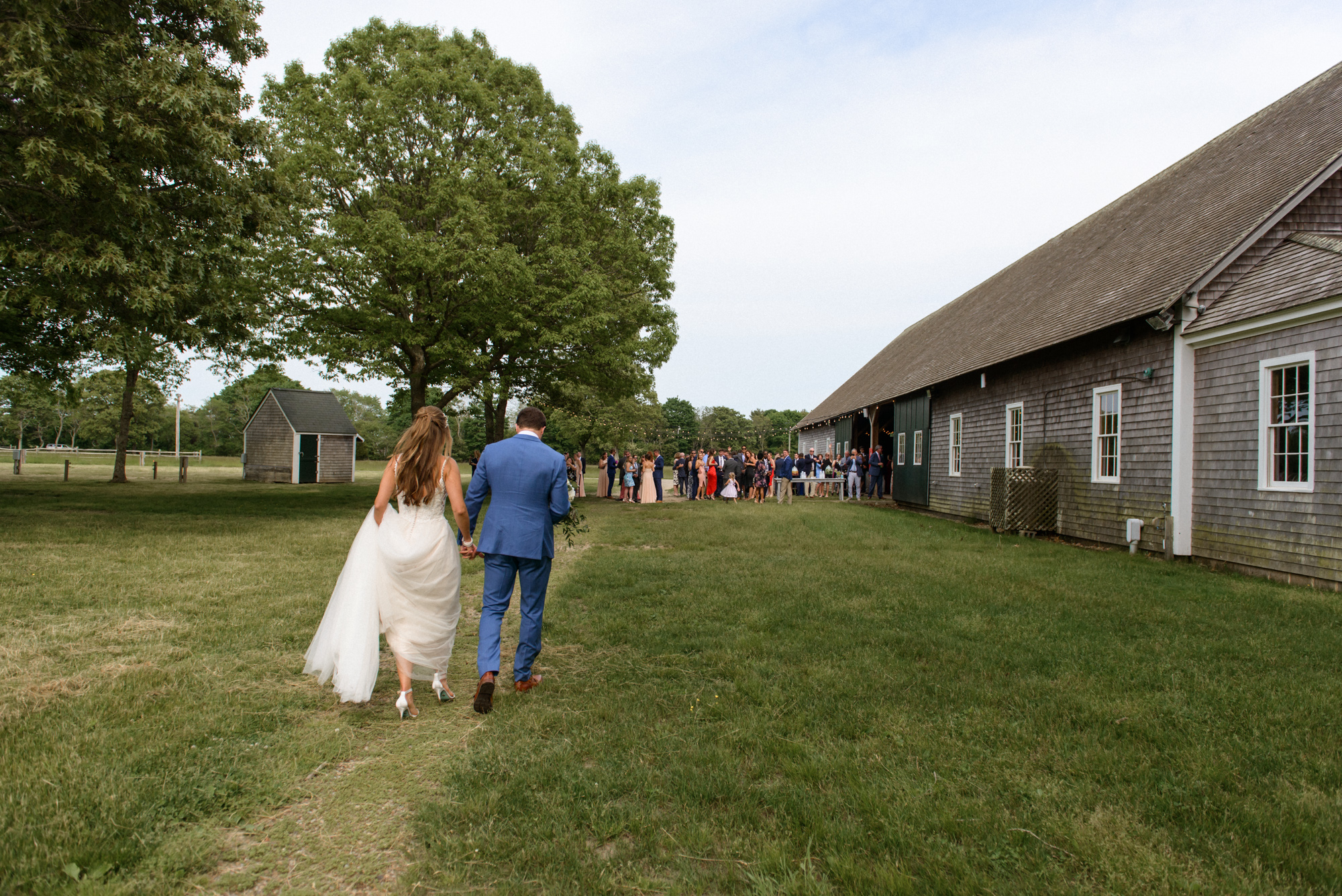 A bride and groom walking at the Martha's Vineyard Agricultural Hall in West Tisbury photo by David Welch Photography