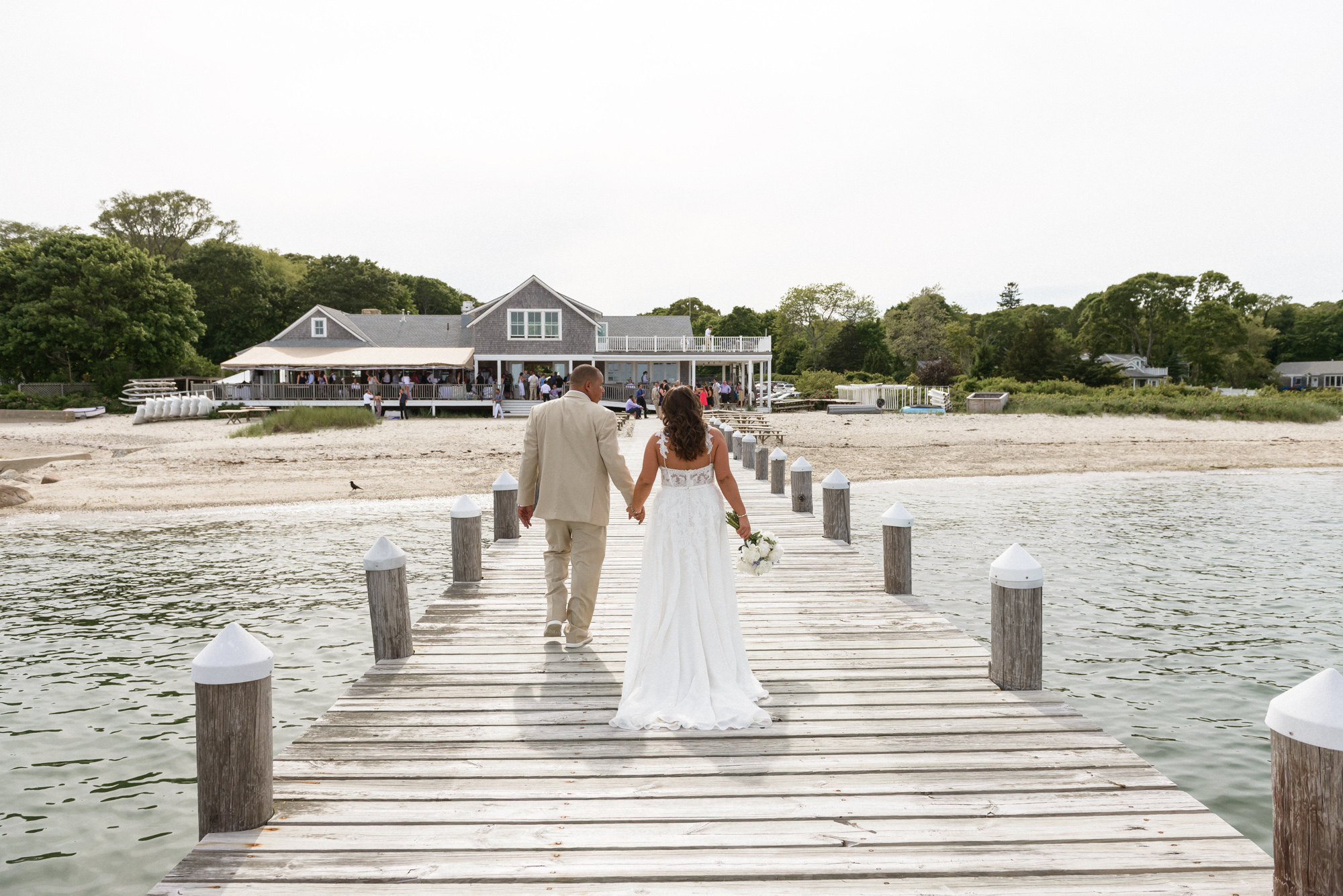 A bride and groom walking on a pier at the Vineyard Haven Yacht Club martha's vineyard wedding venues photo by David Welch Photography