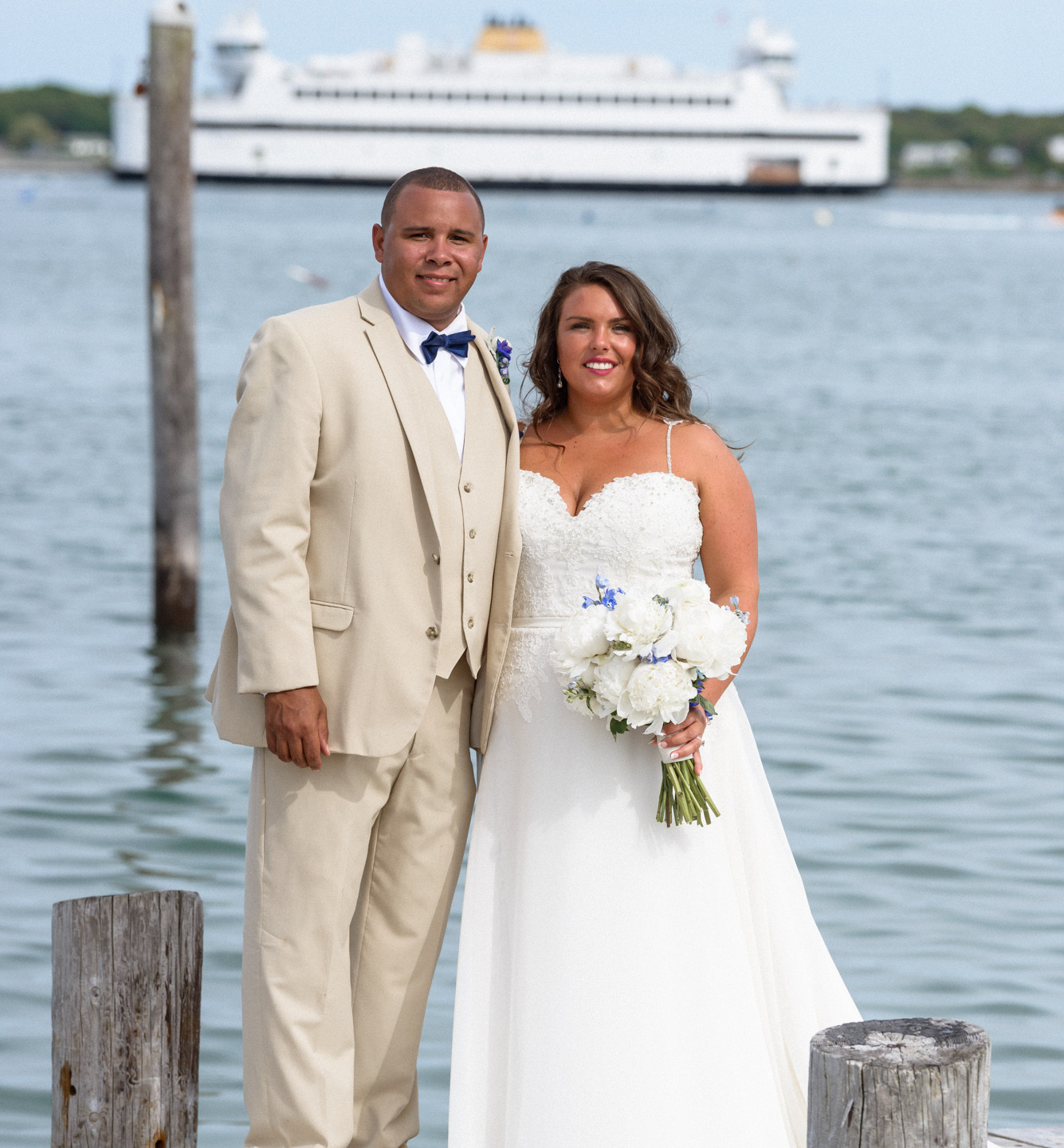 A bride and groom pose for a photo at the Vineyard Haven Yacht Club photo by David Welch Photography