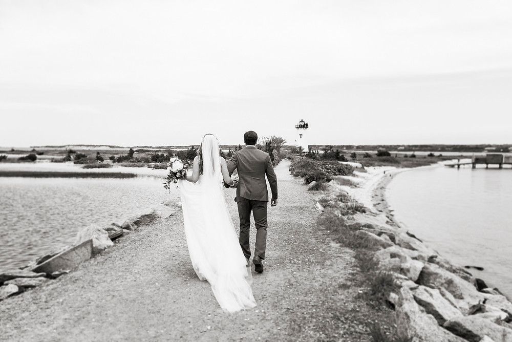 A bride and groom walk towards the Edgartown Lighthouse photo by David Welch Photography