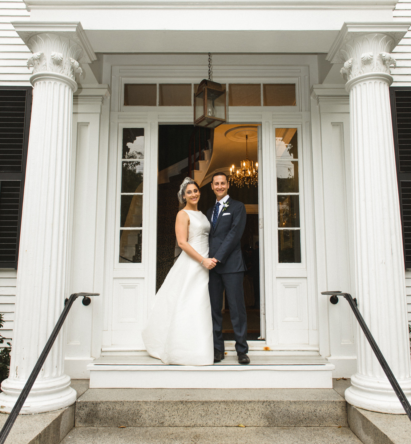 A bride and groom stand on the steps of the Dr. Daniel Fisher House in Edgartown photo by David Welch Photography