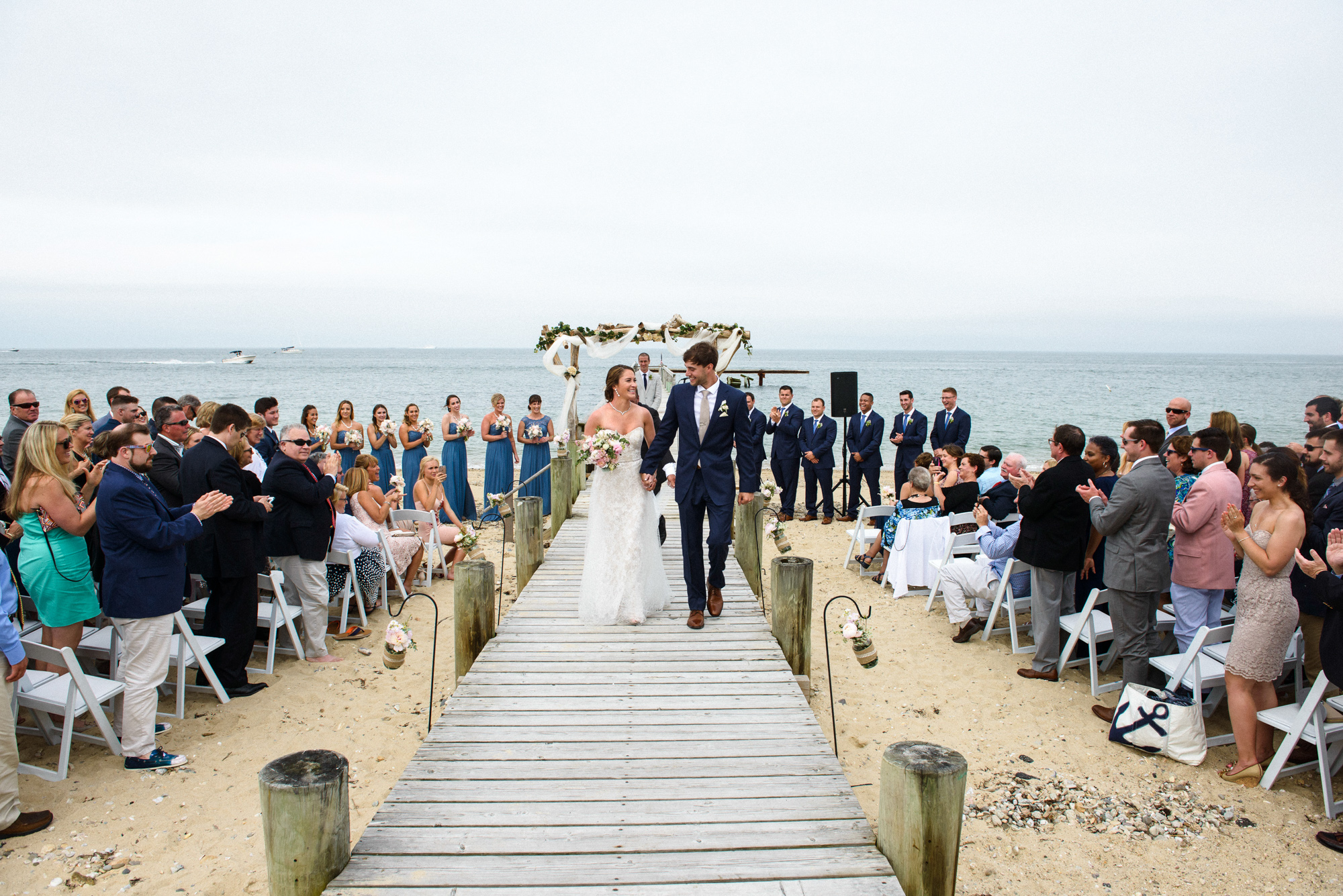 A bride and groom exit their wedding ceremony at the East Chop Beach Club in Oak Bluffs photo by David Welch Photography