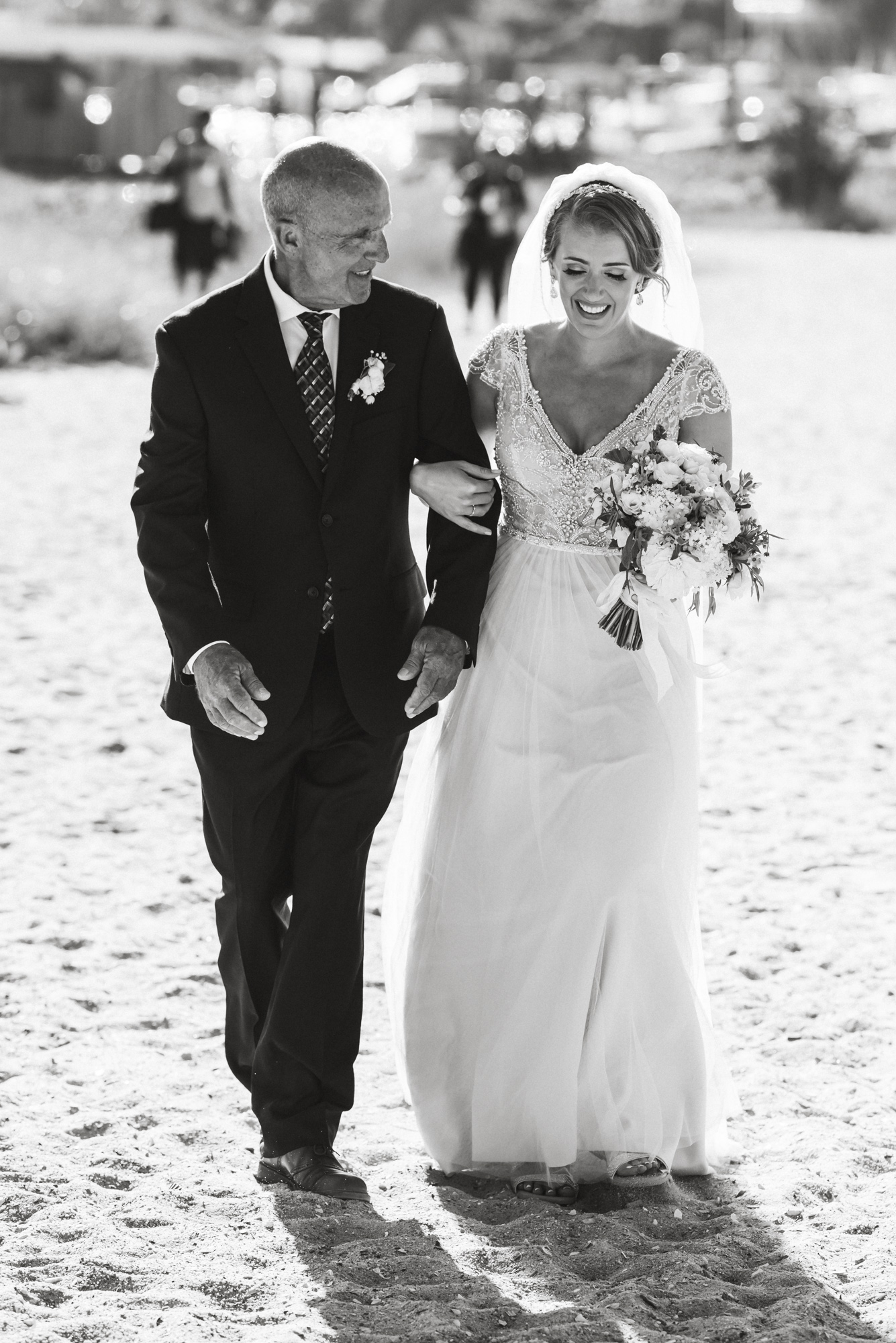 A father escorts his daughter to her wedding by the Edgartown Lighthouse photo by David Welch Photography