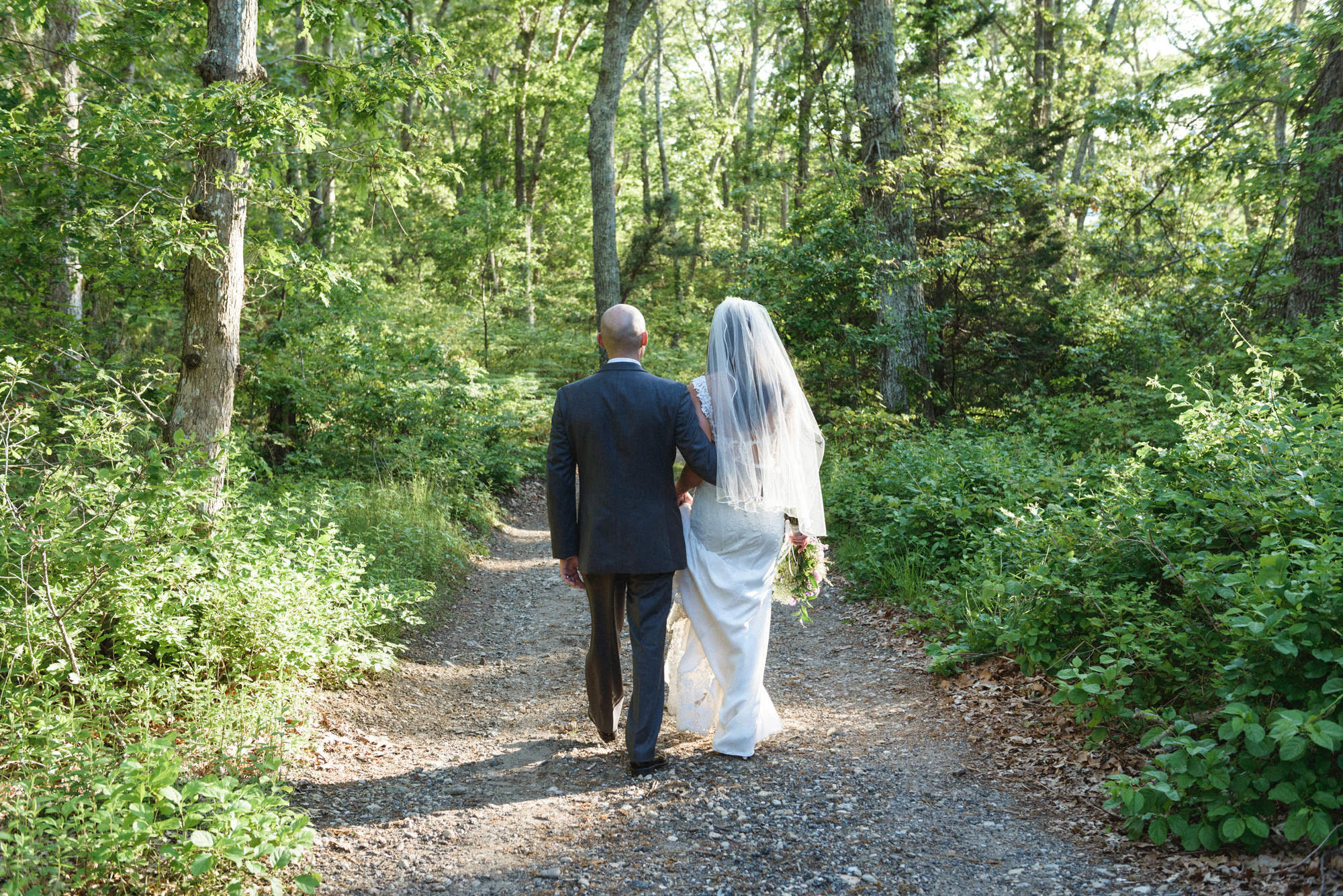 A bride and groom walking on a trail at the Sailing Camp Park in Oak Bluffs photo by David Welch Photography