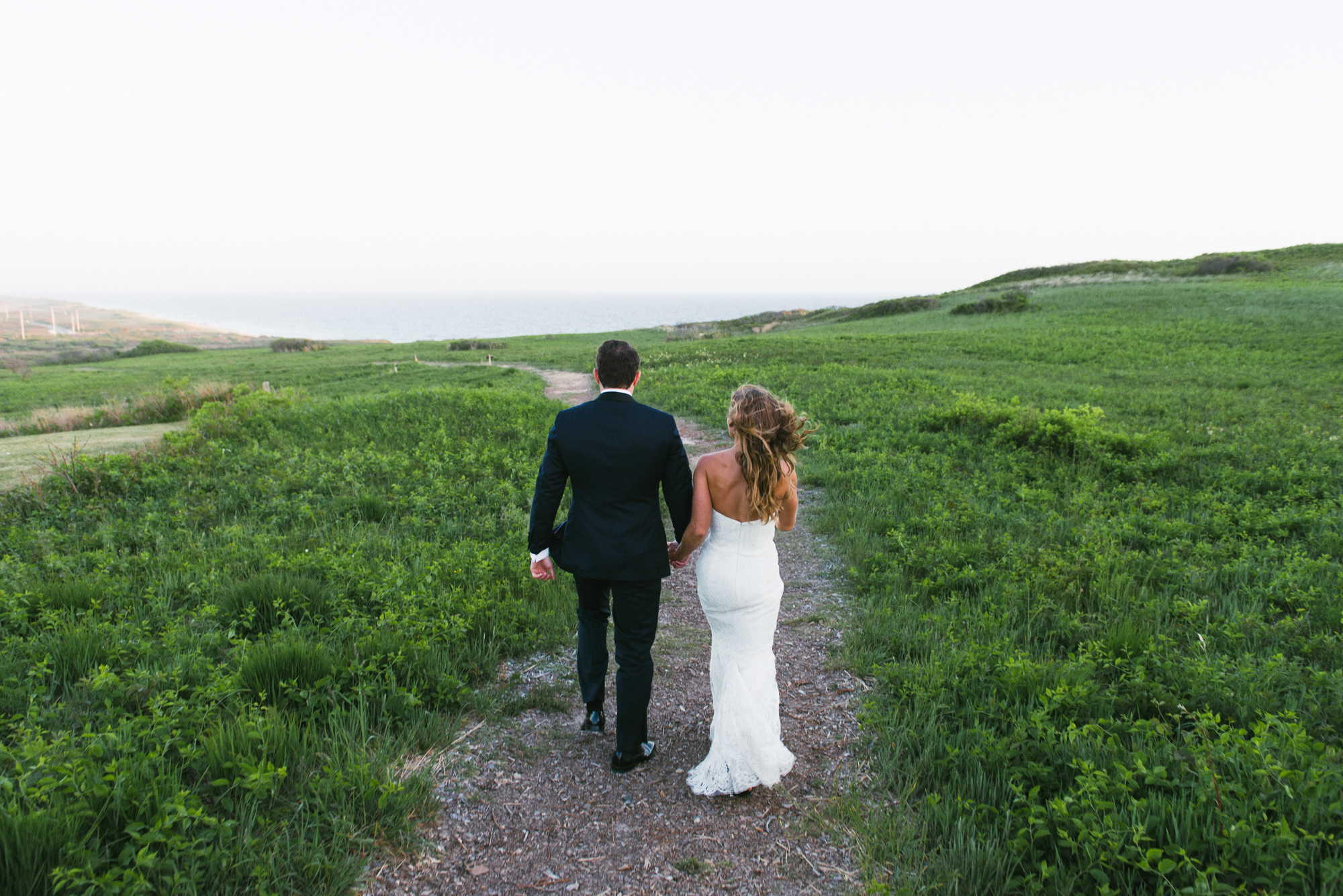 A bride and groom on a walking path outside the Vanderhoop Homestead in Aquinnah A bride and groom at a martha's vineyard wedding venues West Chop Club photo by David Welch Photography photo by David Welch Photography