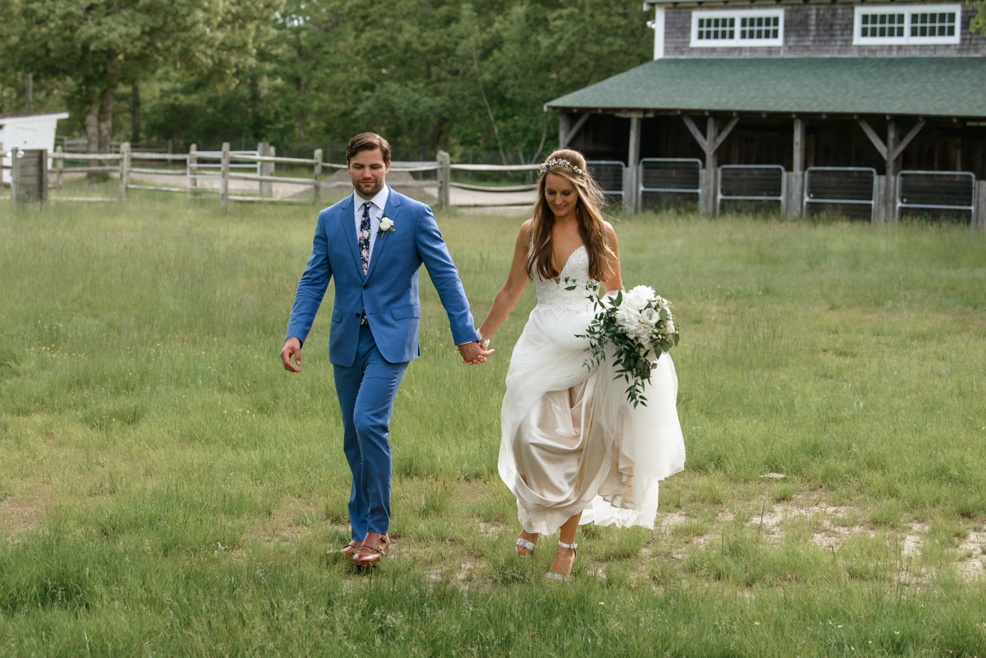A bride and groom walk hand in hand in a field at the Martha's Vineyard Agricultural Hall in West Tisbury photo by David Welch Photography