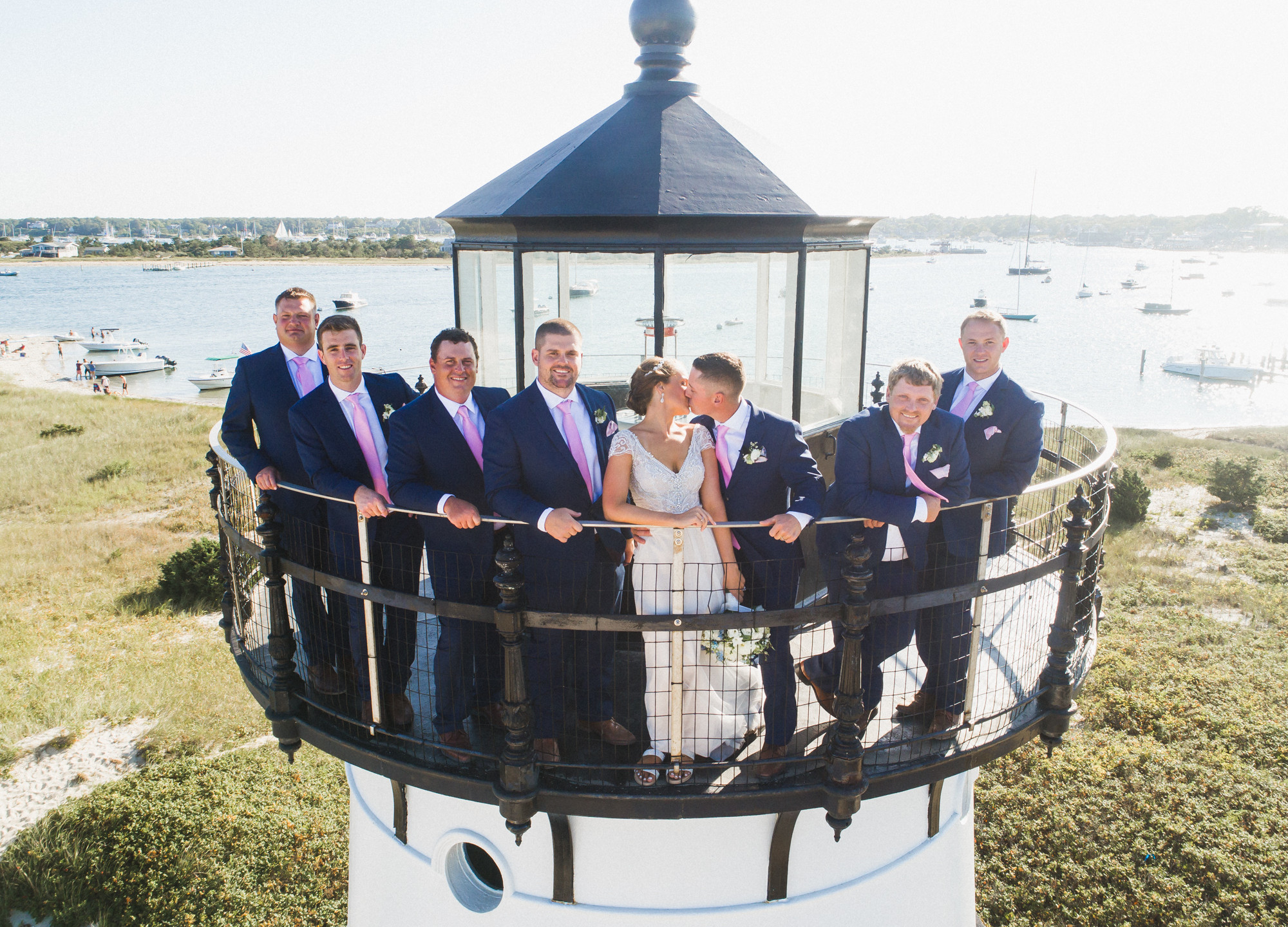 A bride and groom with his groomsmen atop the Edgartown Lighthouse photo by David Welch Photography