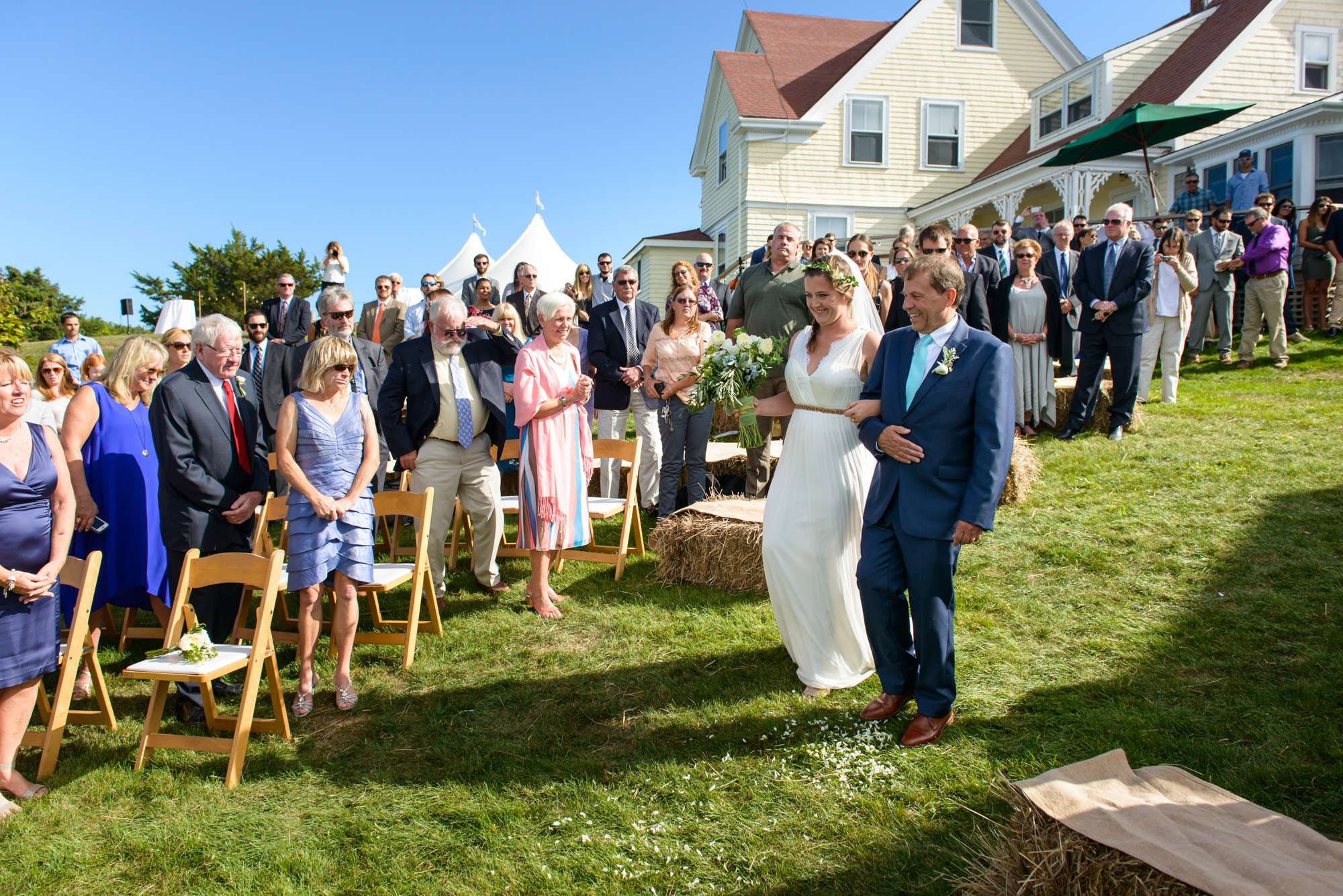 A father escorts his daughter to her wedding ceremony at The Tower House in Chilmark photo by David Welch Photography