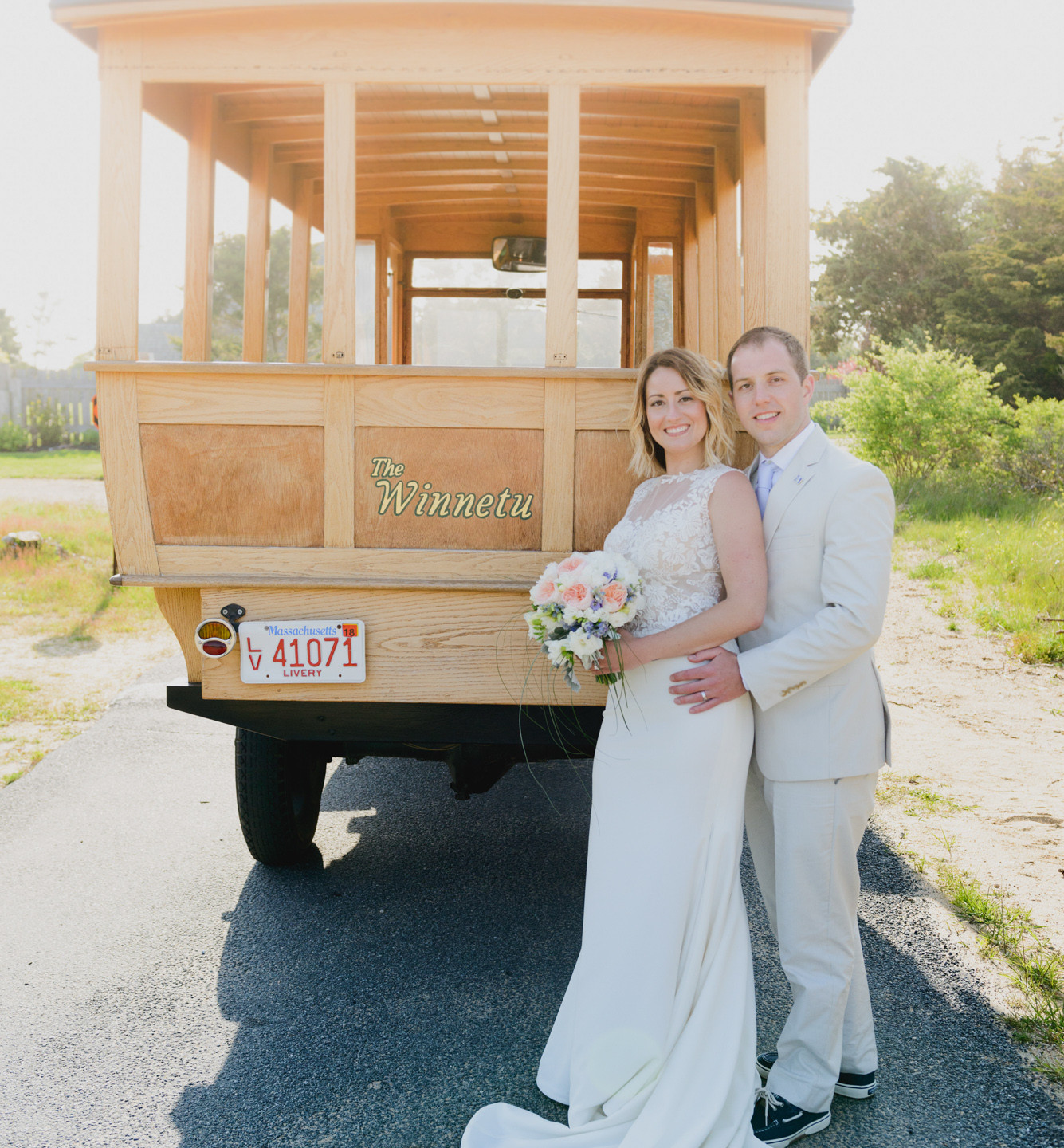 A bride and groom pose with the Winnetu Oceanside Resort wagon  photo by David Welch Photography