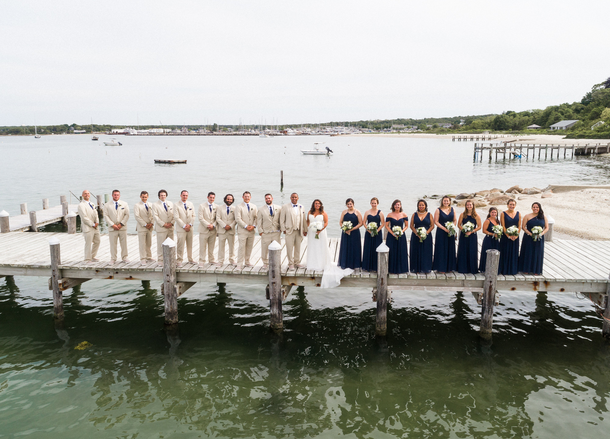 A drone photo of a large wedding party on the pier at the Vineyard Haven Yacht Club on Martha's Vineyard photo by David Welch Photography