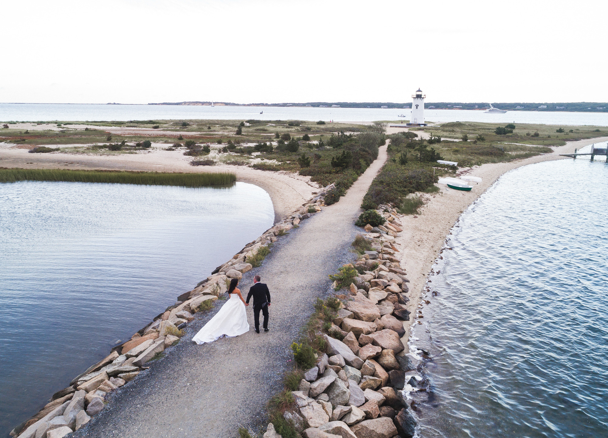 A bride and groom walk the jetty towards the Edgartown Lighthouse photo by David Welch Photography