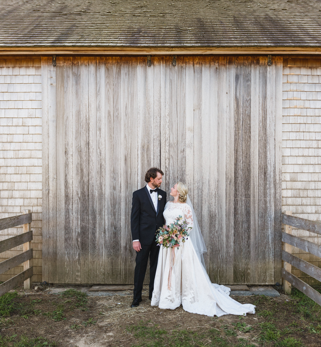 A bride and groom against a rustic barn at Island Alpaca Company martha's vineyard wedding venues photo by David Welch Photography