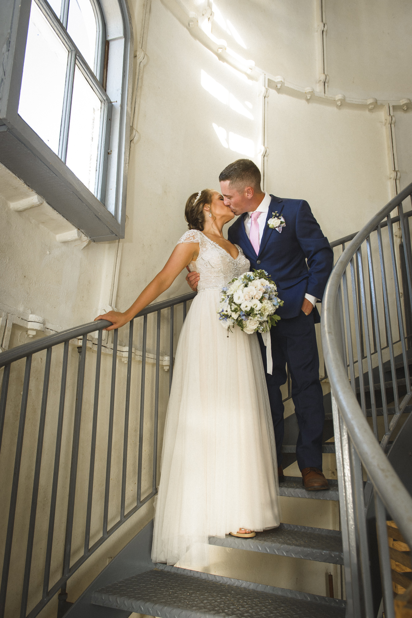 A bride and groom pose for a photo inside the Edgartown Lighthouse photo by David Welch Photography