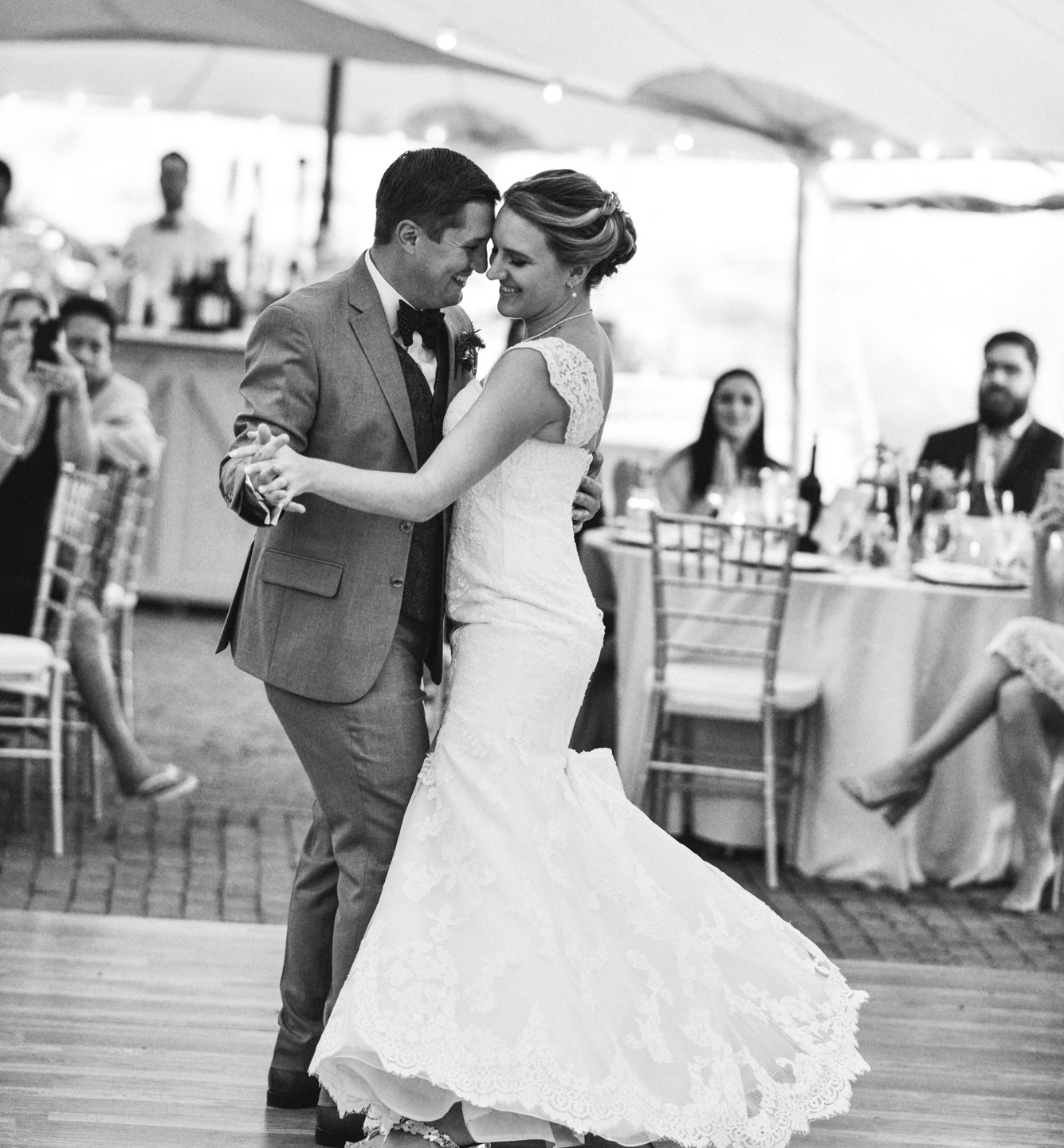 A bride and groom share a first dance under a Sperry pole tent at Farm Neck Golf Club  photo by David Welch Photography