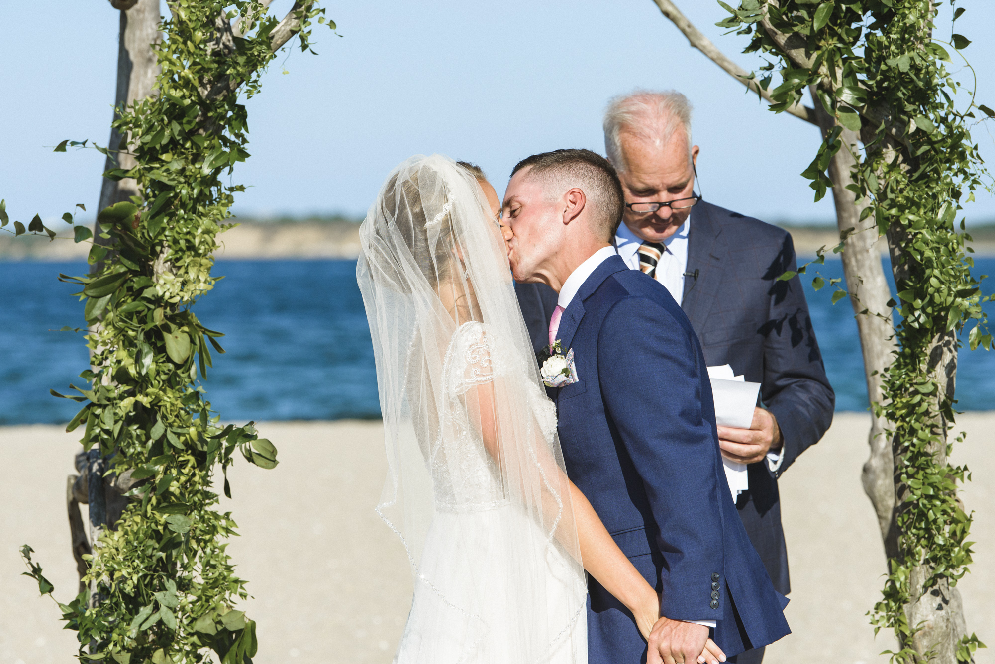 Newlyweds kiss at their wedding ceremony at the Edgartown Lighthouse photo by David Welch Photography