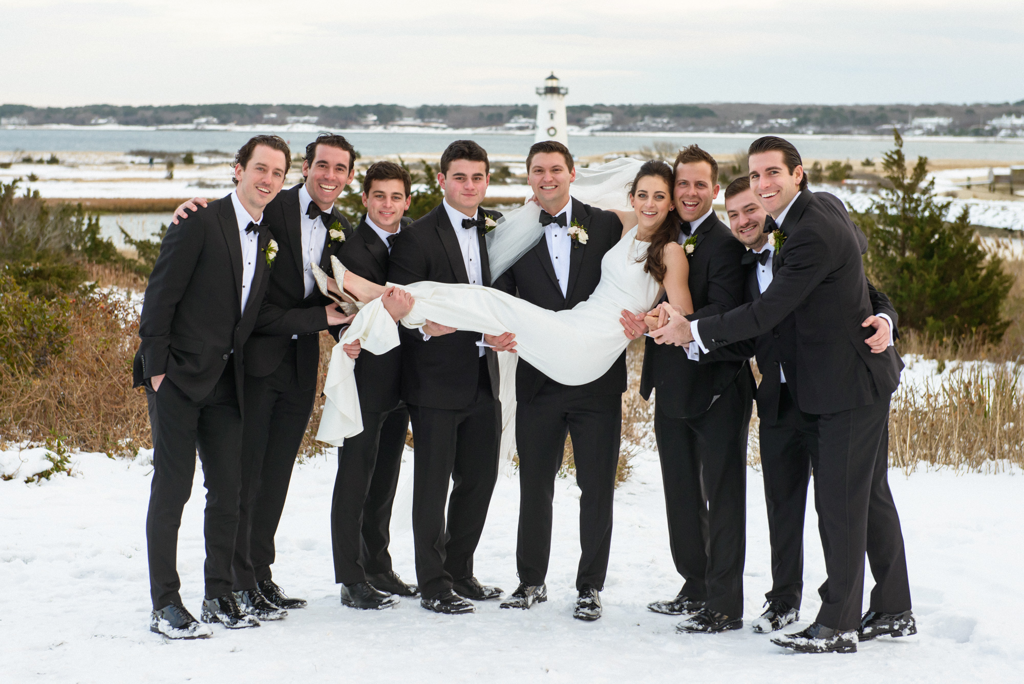 A groom and his groomsmen hoist a bride on a snowy day in Edgartown across from the Harbor View Hotel  photo by David Welch Photography