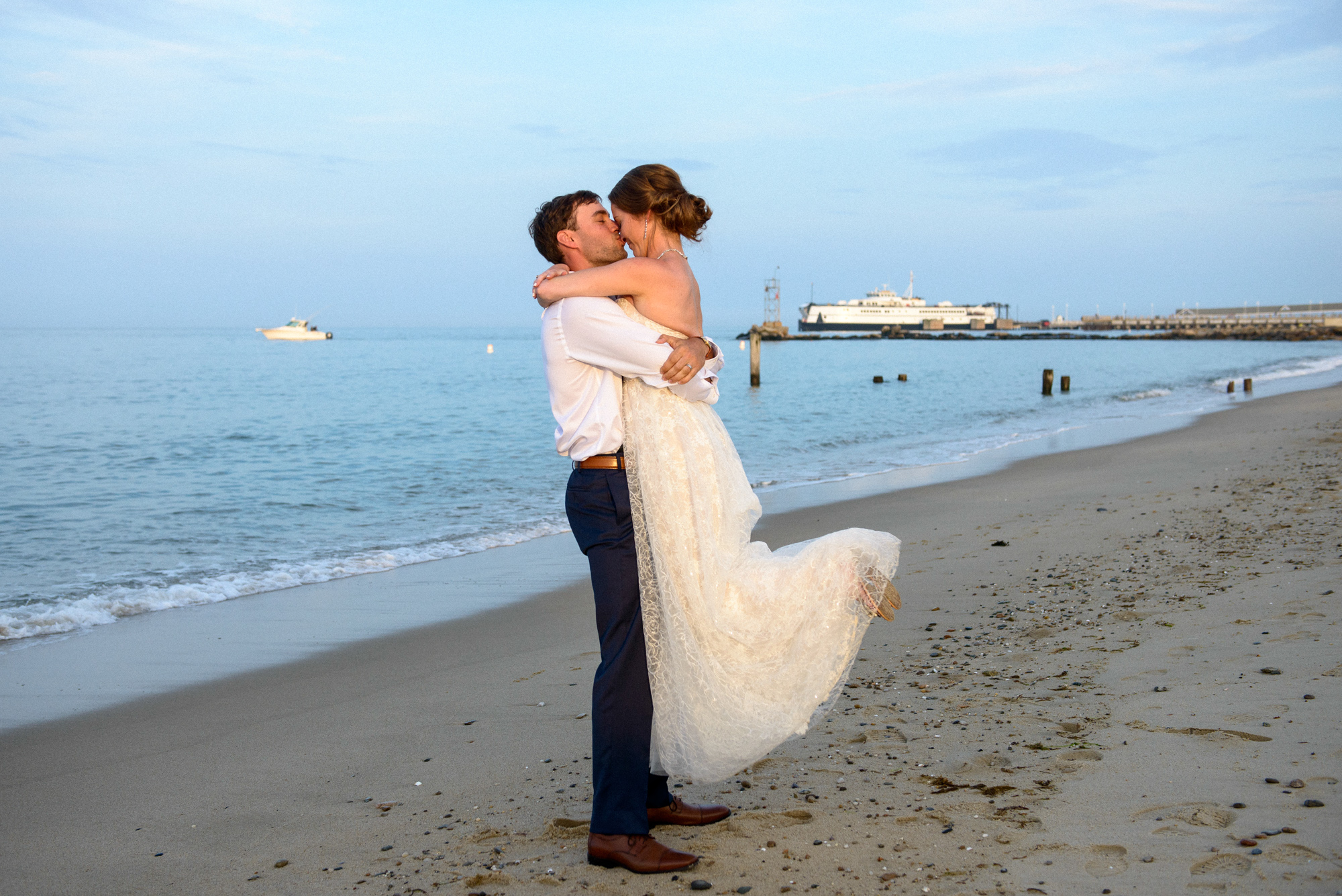 A bride and groom on the beach at the East Chop Beach Club with a view of the Steamship Martha's Vineyard photo by David Welch Photography