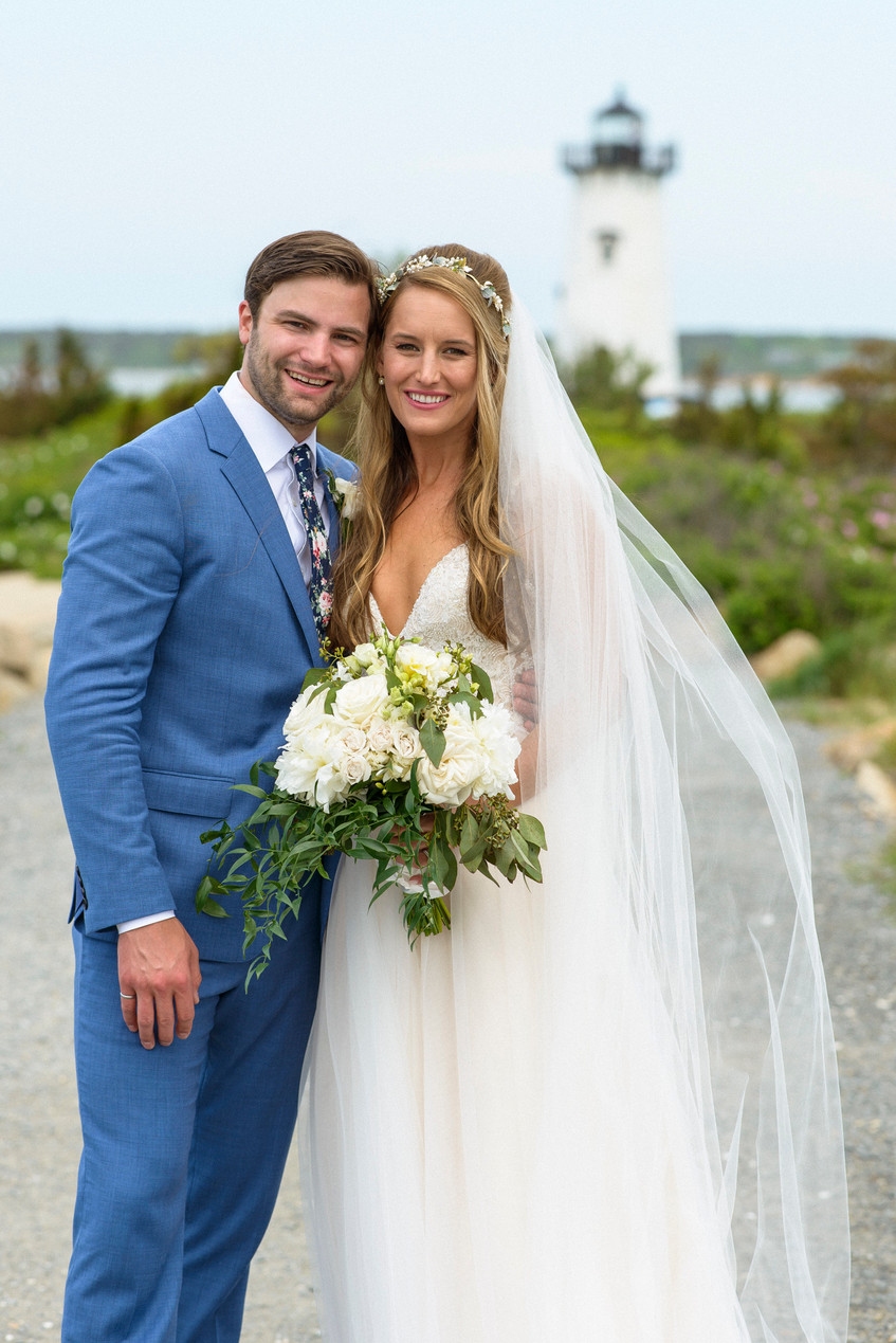A bride and groom pose for a photo near the Edgartown Lighthouse photo by David Welch Photography