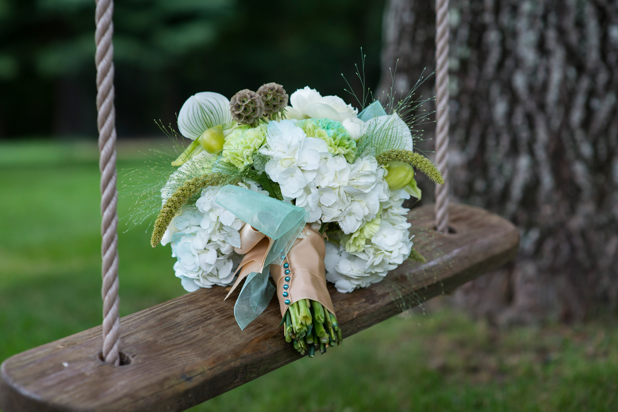 A bridal bouquet on a swing at Lambert's Cove Inn photo by David Welch Photography