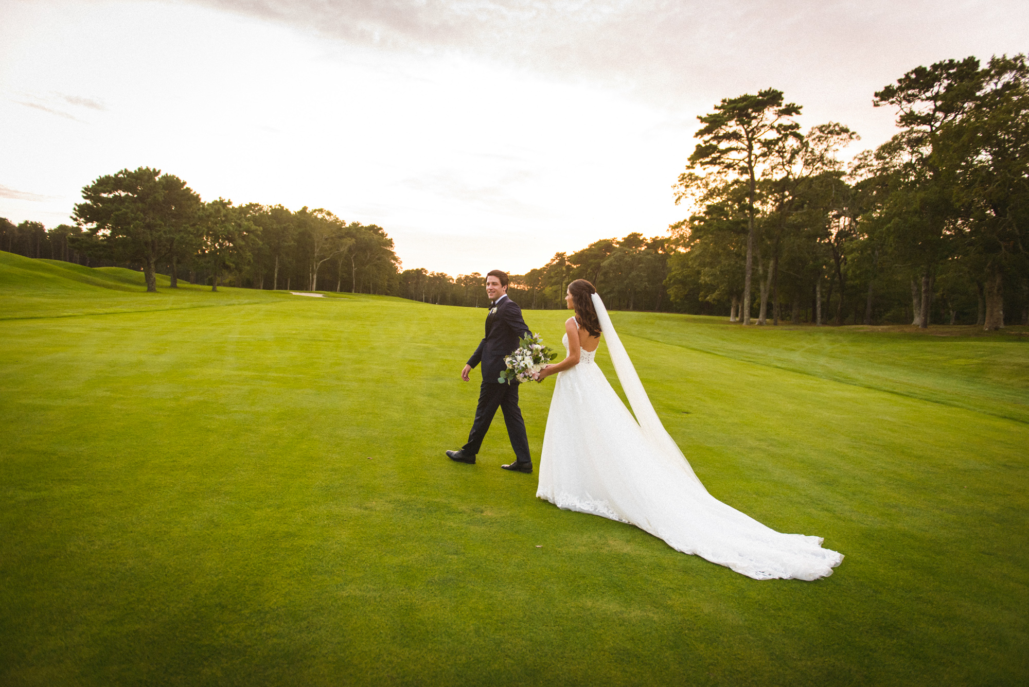 A bride and groom on the green at Farm Neck Golf Club  photo by David Welch Photography