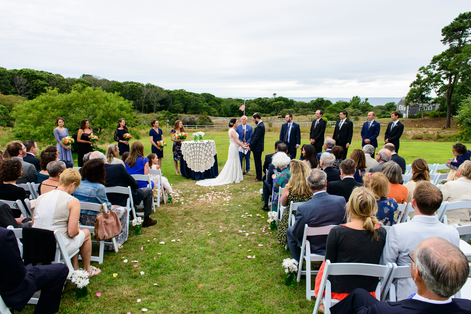 A wedding ceremony in a field at The Beach Plum Inn & Restaurant photo by David Welch Photography
