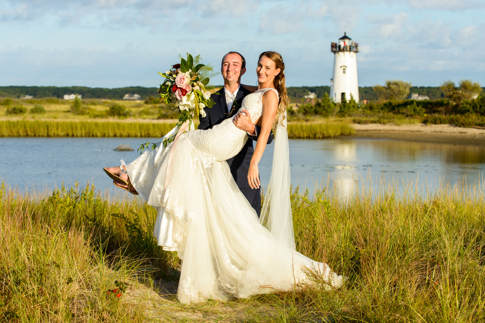 A groom holds his new bride near the Edgartown Lighthouse  photo by David Welch Photography