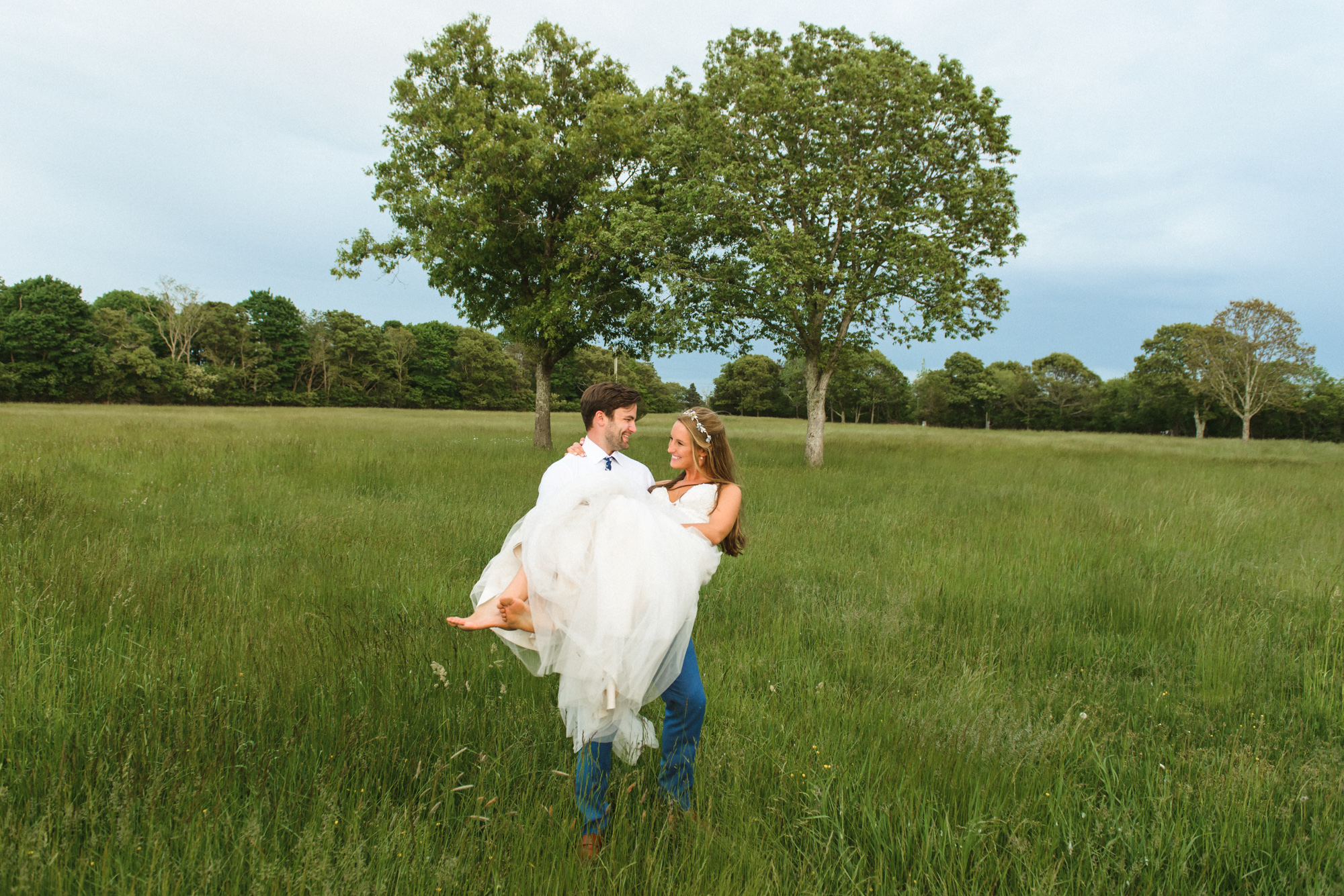 A groom carrying his bride in a field at the Martha's Vineyard Agricultural Hall in West Tisbury photo by David Welch Photography