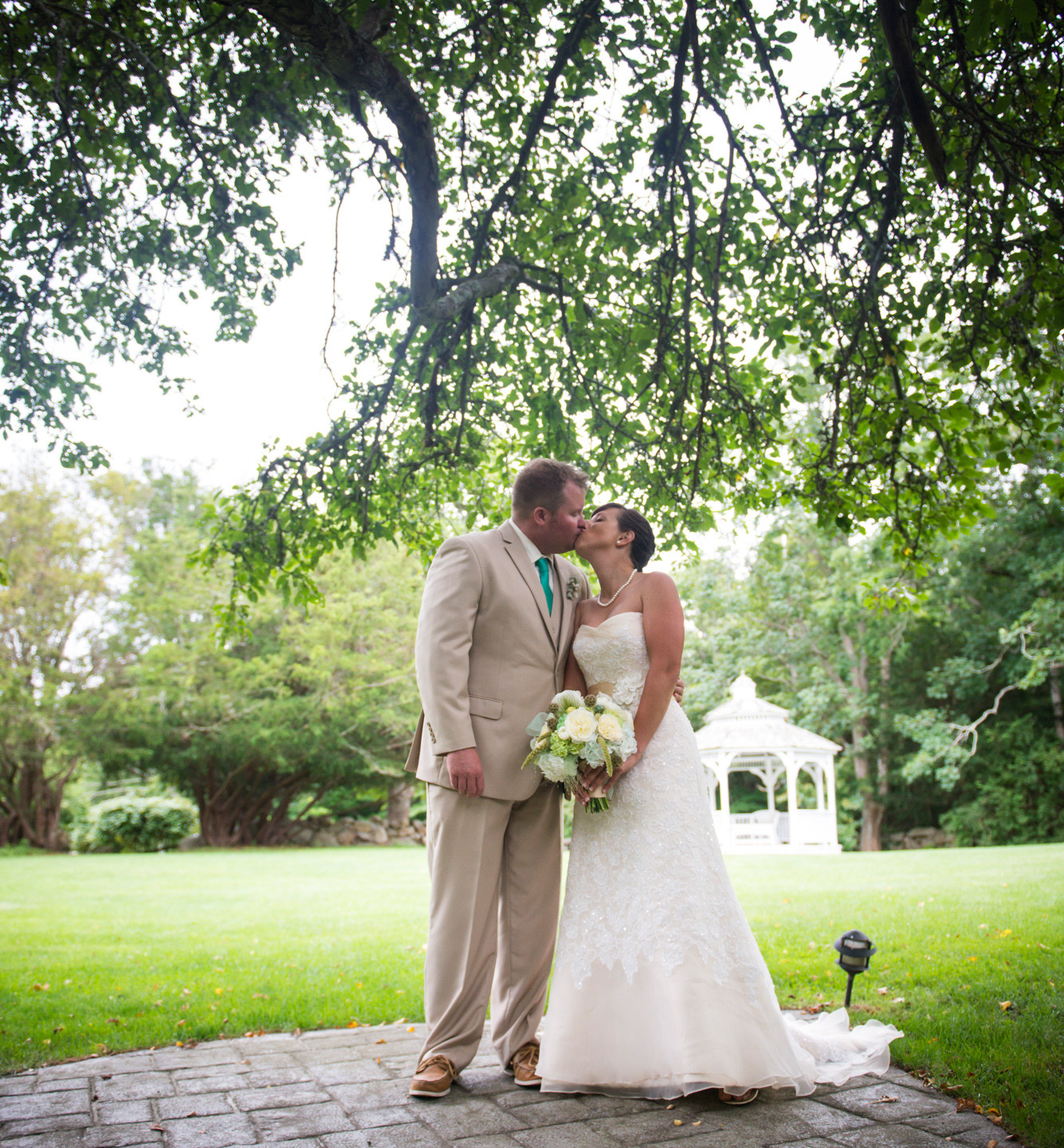 A bride and groom kiss at a magical Lambert's Cove Inn setting photo by David Welch Photography