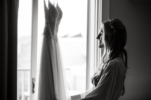 A bride looks at her dress hanging near a sliding door photo by David Welch Photography